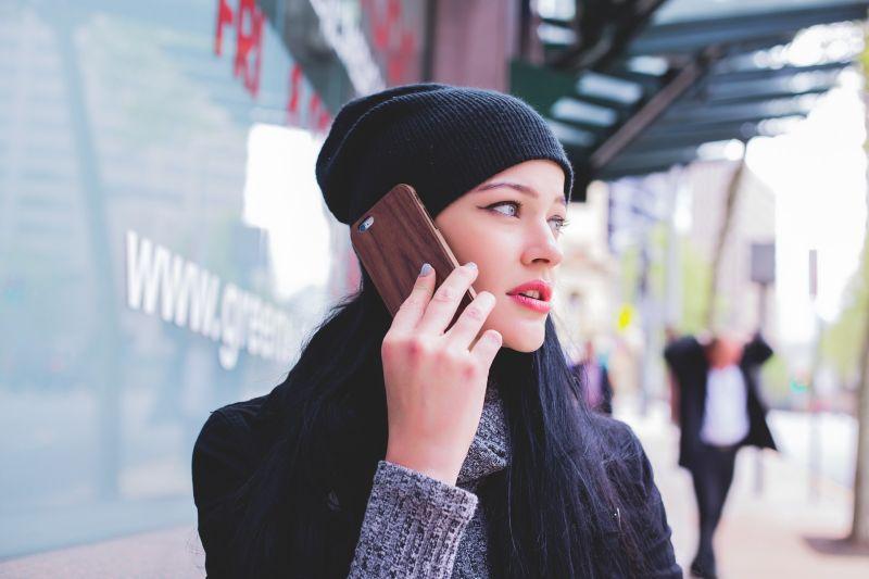 Junge Frau telefoniert auf der Straße mit einem Smartphone
